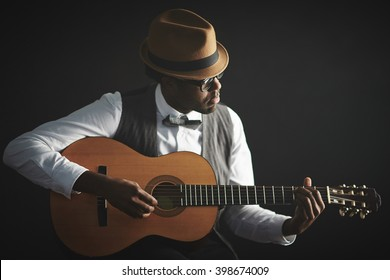 African man playing guitar isolated on black background