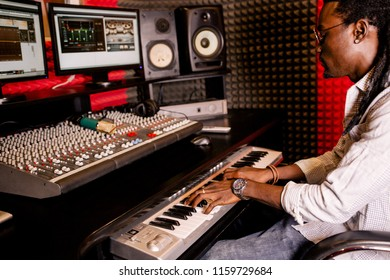 African man playing on synthesizer in recording Studio