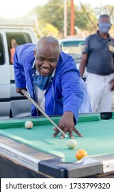 African man playing snooker at the bus rank in Gaborone, free time