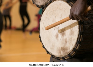 African man playing traditional drum, close up view from left side behind