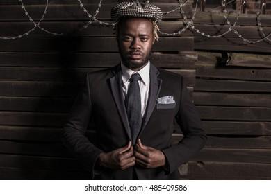 African Man  portrait headshot wearing white shirt, jacket hat and  tie on wooden background