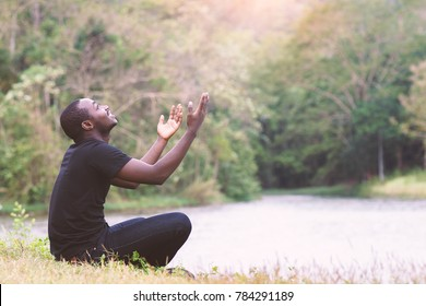 African man praying for thank god with light flare in nature.