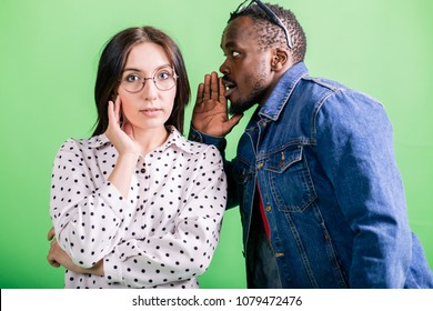African man quietly tells the secret to his girlfriend European appearance standing on a green background