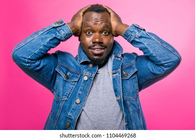African man raised his hands to his head standing in the Studio on a pink background