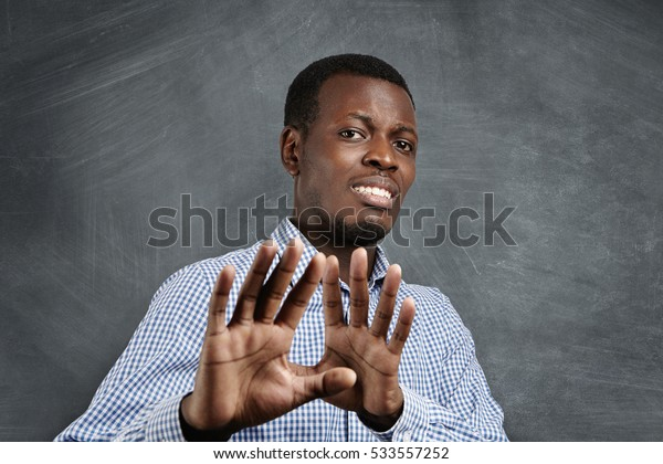 African man with scared expression on his face making frightened gesture with his palms as if trying to defend himself from someone. Fearful dark-skinned man asking to stop, gesturing with his hands