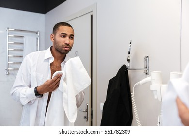 African man in shirt washes in bathroom in hotel