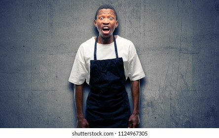 African man shop owner wearing apron stressful, terrified in panic, shouting exasperated and frustrated. Unpleasant gesture. Annoying work drives me crazy