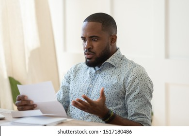African man sit at table hold letter read awful rejection news about dismissal company discrimination, student received failed test notice, financial money problem, high domestic bills or debt concept
