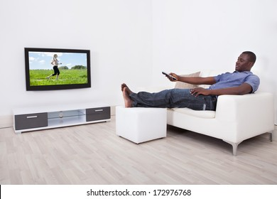 African Man Sitting On Sofa With Remote Holding In Hand