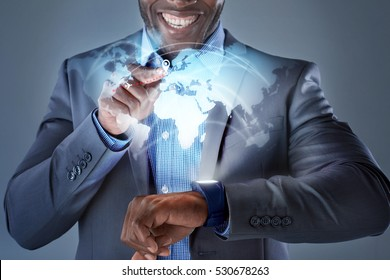 African man smiling while pressing smartwatch displaying globe hologram wearable technology futuristic business travel concept