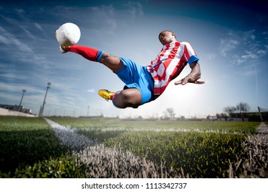 African man soccer player hitting the ball.