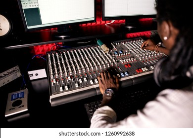 African man sound engineer with headphones at work. rear view