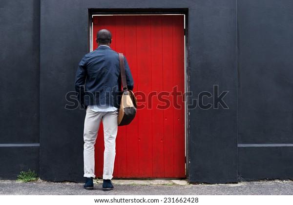 african man standing at red door in city