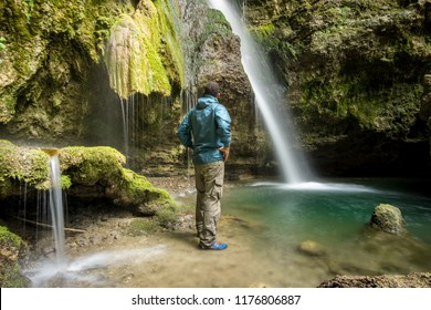 African man standing with wet rain jacket in waterfall canyon. Hinanger Wasserfall, Allgau, Bavaria, Germany.