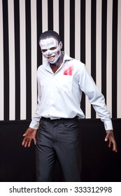 African man a striped background. White and black bands as a symbol of good and evil, good and bad. Zebra. Fashion man in the role of zombie or voodoo. Stylish african man. Halloween. Party, Carnival.