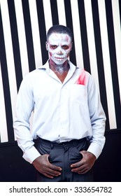 African man a striped background. White and black bands as a symbol of good, evil, bad. Zebra. Fashion man in the role of zombie, voodoo. Stylish african man. Halloween. Party, Carnival. Skeleton man.