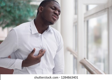 African man suffering from acid reflux or GERD; sick stressed black man with indigestion, acid reflux or gerd symptoms; man health care, body care, sickness, pain concept; adult african man model