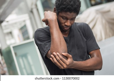 african man suffering from elbow pain; sick black man with elbow joint pain, osteoporosis, bone arthritis, gout, symptoms; body sickness, health care or pain concept; adult african man or model