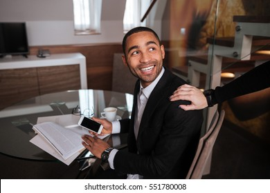 African man in suit sitting by the table and meets his friend in hotel
