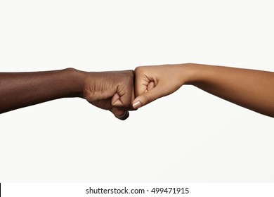 African man touching knuckles with dark-skinned woman as sign of agreement, partnership and cooperation. Two people holding hands in fist bump while greeting each other in informal modern handshake