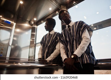 African man in traditional clothes and glasses at elavator or modern lift.