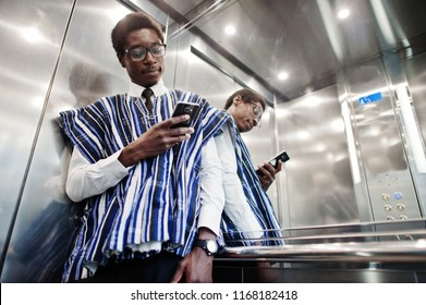 African man in traditional clothes and glasses with mobile phone at elavator or modern lift.