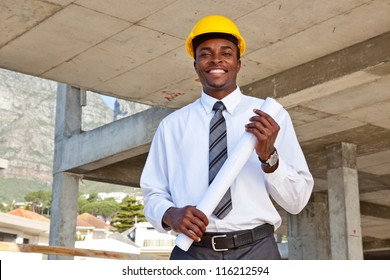 African man wearing a hard hat in a construction site holding building plans