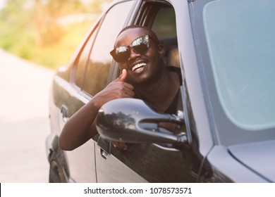 African man wearing sunglasses and smiling while sitting in a car with open front window.