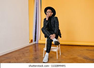 African man in white sneakers sitting on chair in studio. Indoor photo of pensive black guy wears trendy dark-gray suit.