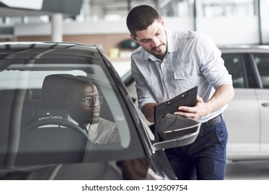 An African man who buys a new car checks a car talking to a professional vendor