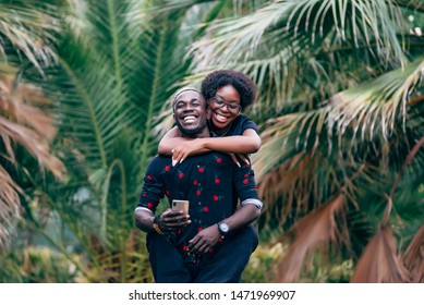 African man and woman having fun with mobile phone among palm trees.
