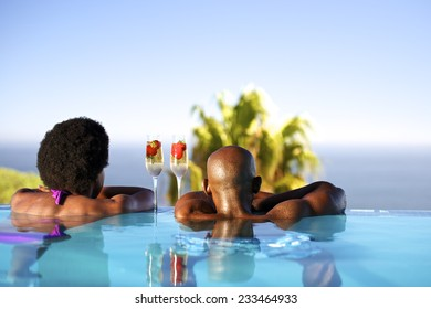 African man and woman in an infinity edge pool over looking the ocean.