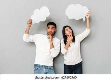 African man and woman looking up and holding empty bubbles isolated