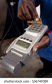 African man's hand, swiping a credit card through a wireless credit card terminal in a fuel station's forecourt.