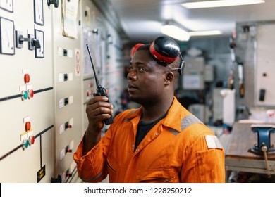 African marine engineer officer in engine control room ECR. He speaks with VHF or UHF portable radio. Ship communication routine