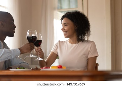 African married couple in love sit at table in kitchen celebrating life event or wedding anniversary holding glasses with red wine clinking toasting feels happy, spouses enjoying romantic date concept