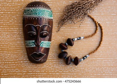 African mask with necklace and decorative branch. Tribal jewelry.