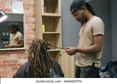 African master hairdresser  making dreadlocks for young woman in hair salon