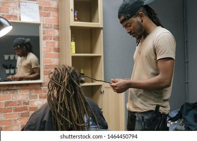 afrikanischer Friseur, der im Friseursalon für junge Frau Dreck macht