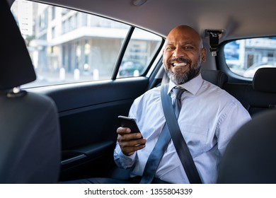 African mature businessman holding smartphone while looking at camera. Successful entrepreneur wearing blue tie sitting in car using mobile phone. Happy formal black business man traveling in taxi.