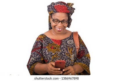african mature woman in loincloth standing on white background looking at mobile phone while smiling.