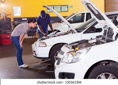 african mechanic and female customer in front her car with bonnet open