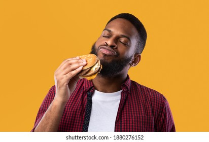 African Millennial Guy Smelling Tasty Burger Standing On Yellow Studio Background. Black Man Enjoying Eating Hamburger. Unhealthy Nutrition Habit, Overeating. Junk Food Lover Concept - Shutterstock ID 1880276152
