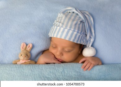 African mixed race baby of 7 days old sleeping in a light blue bed