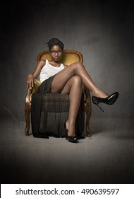 african model sitting on yellow sofa, dark background
