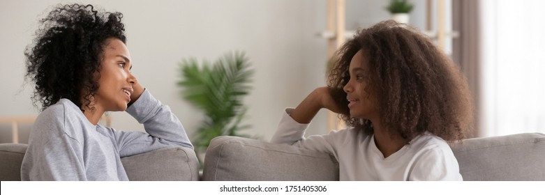African mom chatting with teenage daughter sit on couch in living room. Good relations between diverse generations, understating, motherhood concept. Horizontal photo banner for website header design