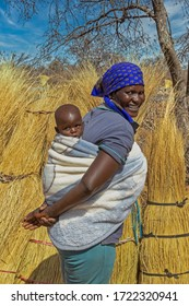African mother carry child in the back in a rural area in her village in Botswana