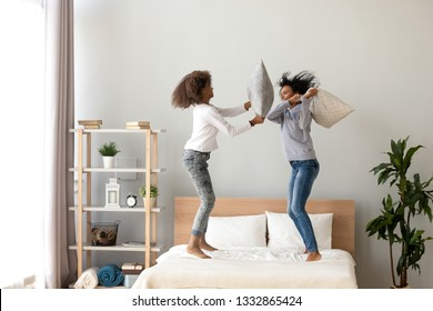 African mother and daughter enjoying pillow fight jumping on bed, babysitter or nanny with teenager girl having fun together at home, older and younger sisters playing, funny leisure activity concept