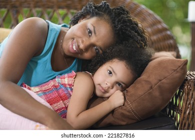 African mother and daughter laying on sofa