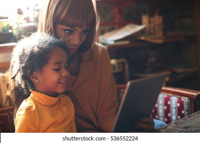 African mother with her smiling daughter using digital tablet at home.